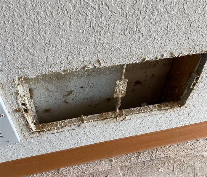 A hole cut into a wall for a vent shows build up and discoloration from nicotine.