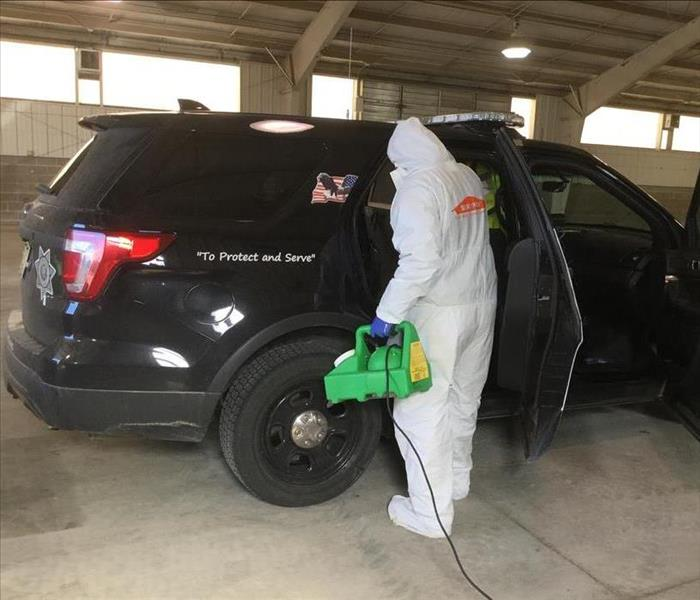 SERVPRO Technician in full protective body suit spraying a chemical