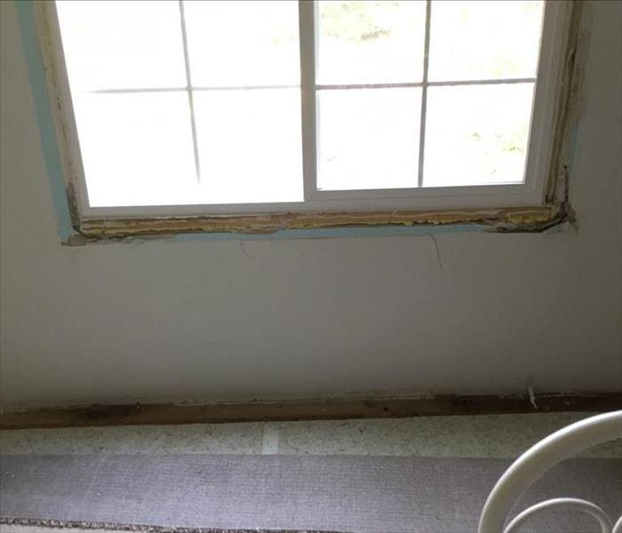 Drywall under a window with water and mold damage