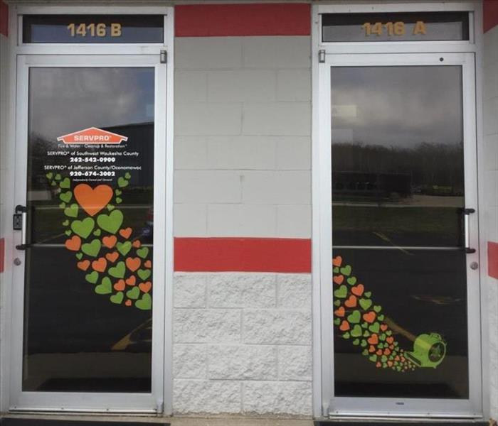 Two glass doors with pictures of orange and green hearts flowing out from an air mover