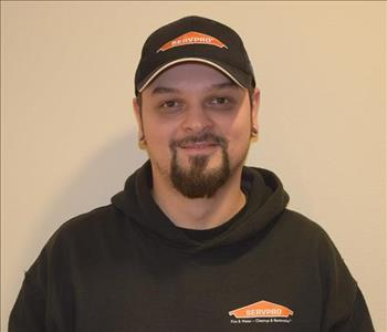 A man wearing a black hat and black SERVPRO hoodie