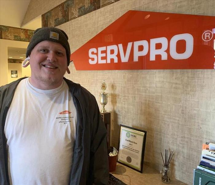Male employee posing in front of SERVPRO sign wearing a white t-shirt