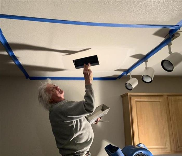 Male worker fixing drywall ceiling by applying drywall mud while standing on ladder
