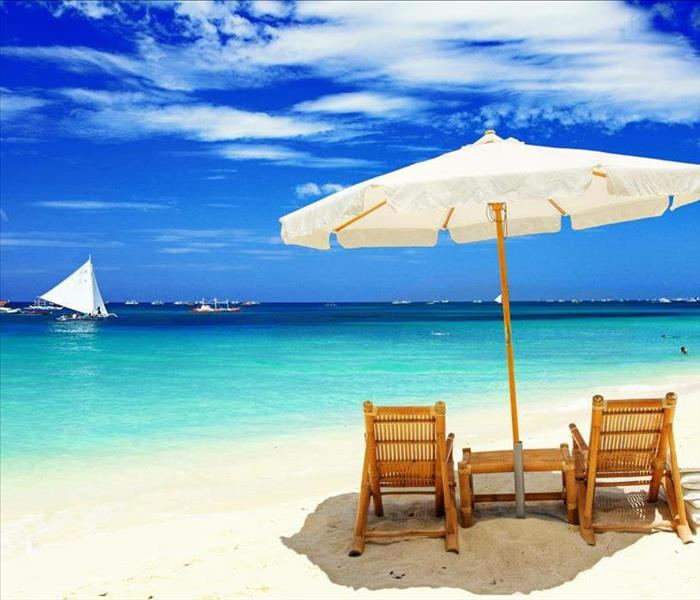 Two bamboo chairs sitting under an umbrella on a sandy beach next to the ocean with boats floating by
