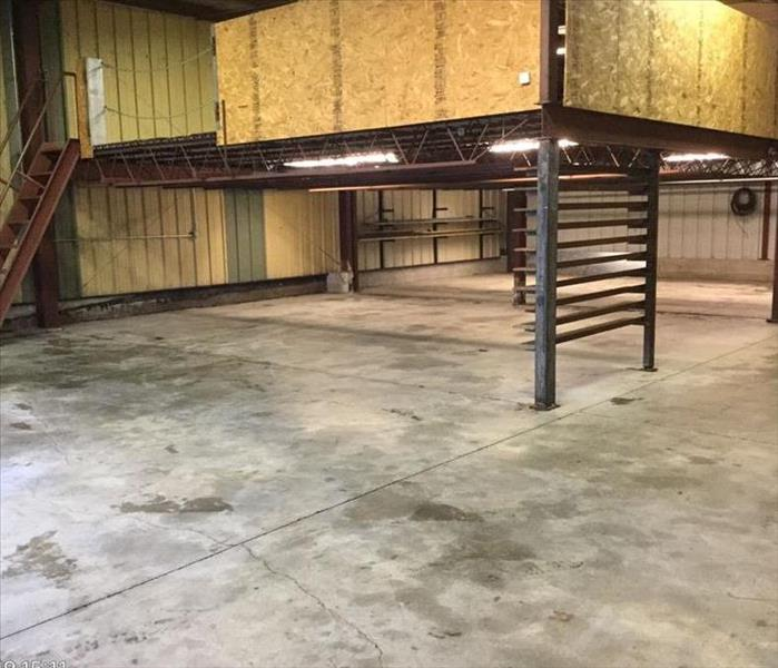 Warehouse with cleaned floor and an empty mezzanine after post cleaning