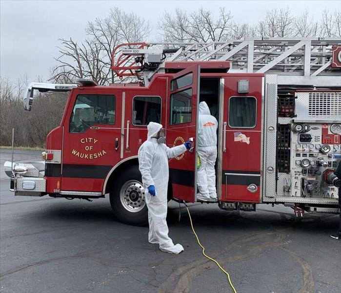 Two people in full personal protective gear disinfecting a fire truck
