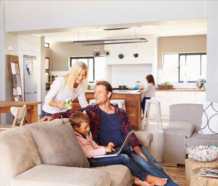 Man and woman and 2 children sitting in living room and kitchen