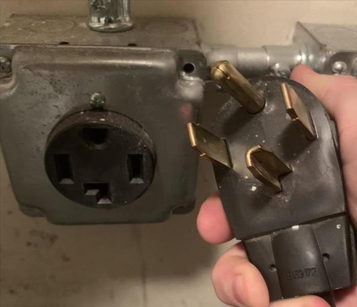 Person hold drying plug next to dryer outlet
