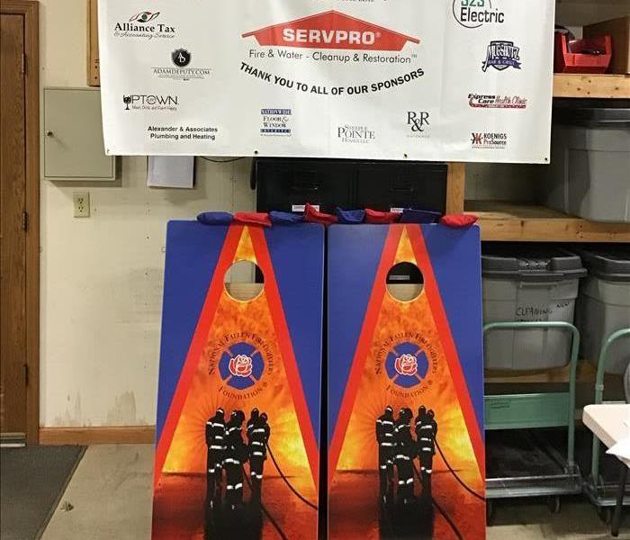 Set of bean bag boards with the National Fallen Firefighters Foundation logo on it and a sign with all 2019 sponsors