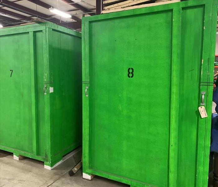 Green wooden crates that are individually numbered sitting in warehouse