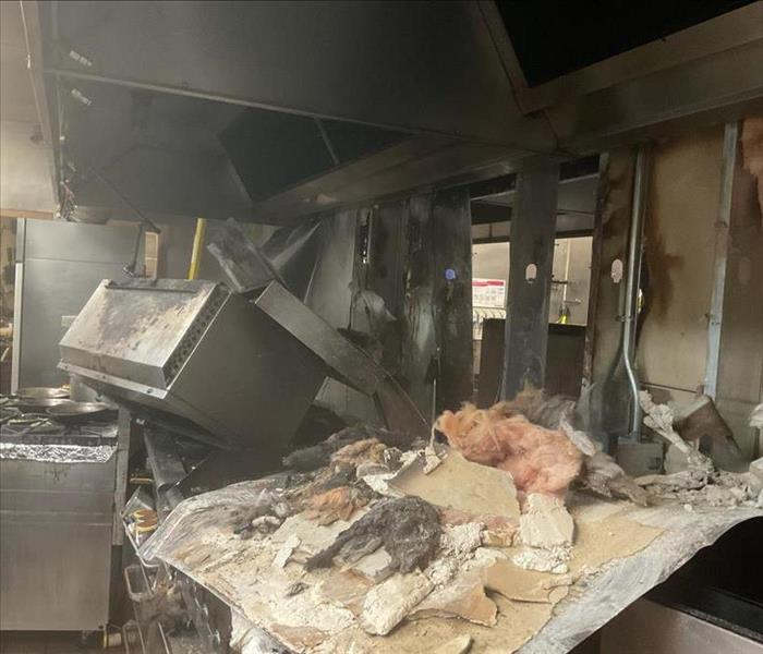 Debris from ceiling and walls laying on the ground after a fire in a commercial kitchen